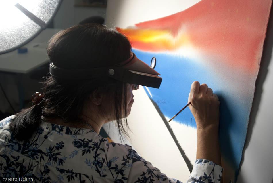 Amparo Escolano, restauradora de paper i pintura, retocant una aquarel·la al seu taller