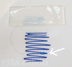 Nanorestore Gel Extra Dry (top) after placing it on top of the ink. The arrow points the drop of solvent, same in which the gel has been soaked without causing any tide-line